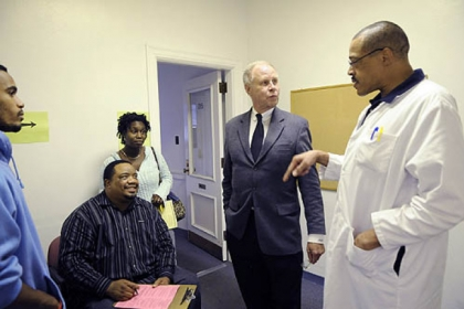 Dr. Dixon, center, meets with nurse practioner Charles Timbers, right, and Dom Timbers, 18, left, his father William Timbers, and Desiree Polite as Dom gets his school vaccinations at the Allegheny County Health Department's Forbes Medical building in Oakland.