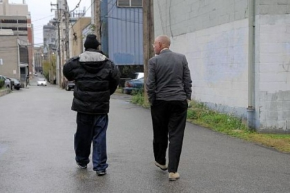 After picking up a patient from his home, Dr. Dixon walks with him to the Forbes Medical building in Oakland.